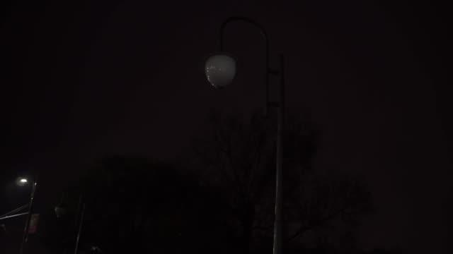 a lantern flickers on a city street, a power outage. night. - проспект стоковые видео и кадры b-roll