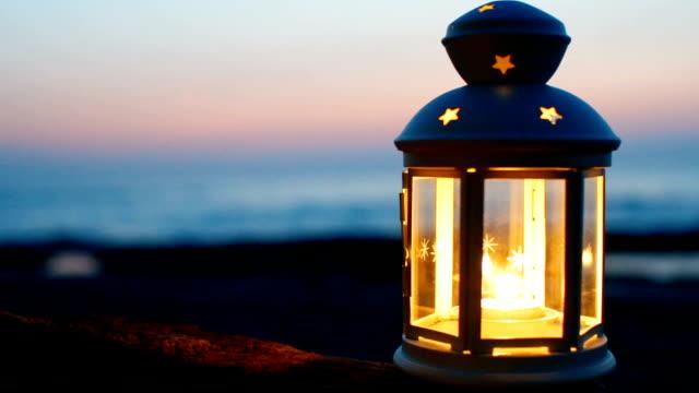 Lantern on Beach at twilight sky glowing lantern with Blurred Seaside sunset background; Sliding shot. lantern stock videos & royalty-free footage