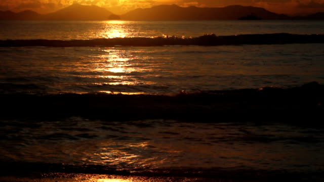 lapping waves at sunset. with sound - sky diving video stock e b–roll