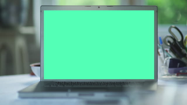 Laptop chroma key Stock video clip showing a close up of a laptop screen in a domestic environment. The chroma-keyed (green screen) display remains static and perfectly square as the camera moves around the laptop with corresponding drift in foreground & background. This is ideal for displaying your own message, advert etc easily dropped in. housing logo stock videos & royalty-free footage