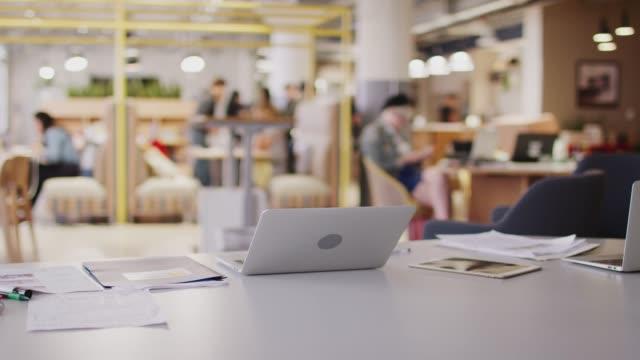 stockvideo's en b-roll-footage met laptop computer en papierwerk op een bureau in een drukke open plan creatieve kantoorruimte, selectieve focus - kleine scherptediepte