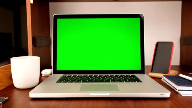 laptop computer with a key green screen set on work home office table