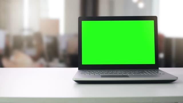 laptop computer with blank green screen on the table in office with people working in blurred background - ekran urządzenia filmów i materiałów b-roll