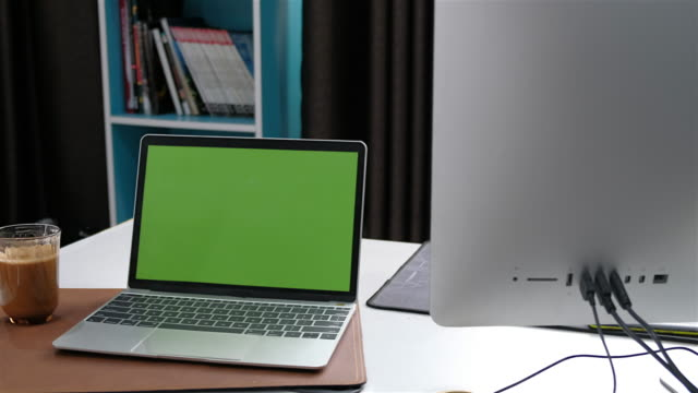laptop green screen on office desk and coffee