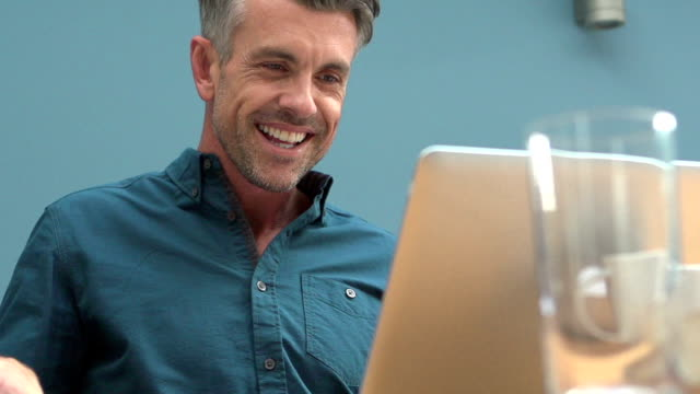 Laptop joy      DE  CM Slow motion clip of a handsome man (40s) very happy at the sight of something on his laptop. test results stock videos & royalty-free footage