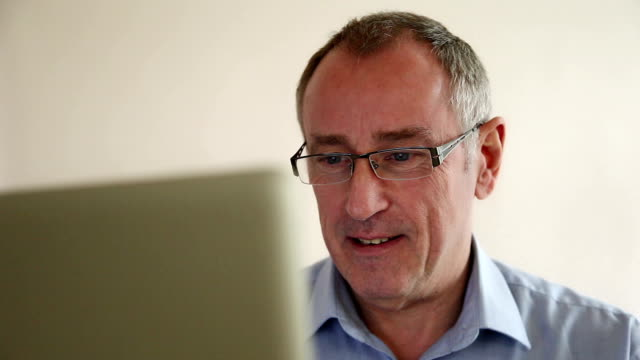 computer portatile di uomo con gli occhiali. - cinquantenne video stock e b–roll