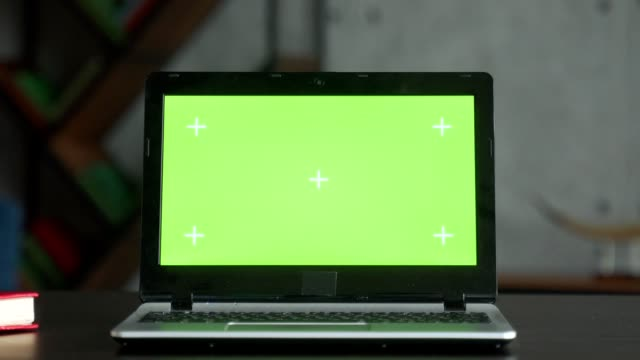 Laptop on the desk in the office shows green screen