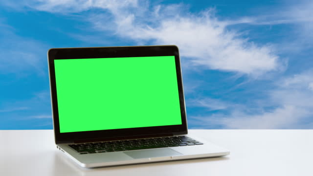 Laptop on the office table over white clouds in blue sky background