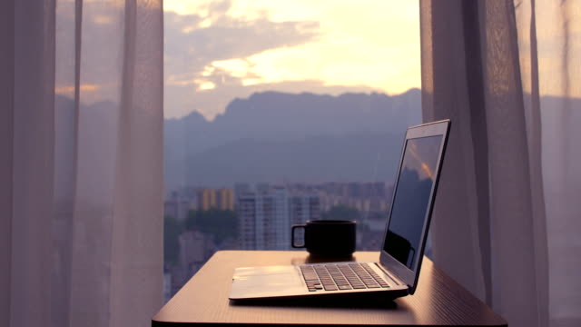 Laptop on wood table by window