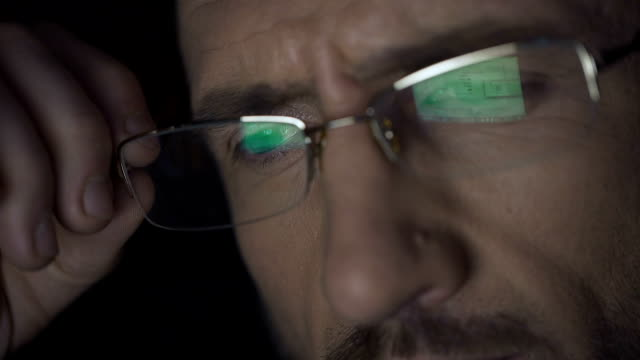 Laptop screen with files reflected in glasses, detective working at night video
