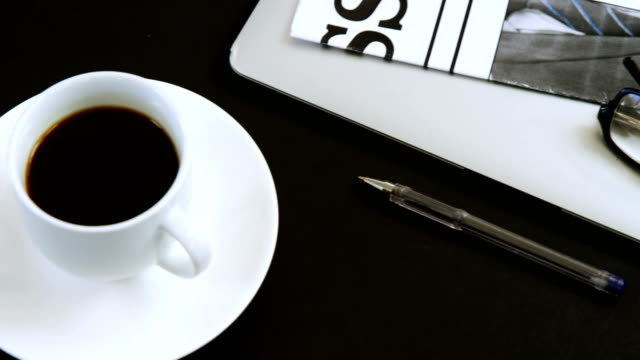 Laptop, spectacles, newspaper, coffee and pen on black background 4k video