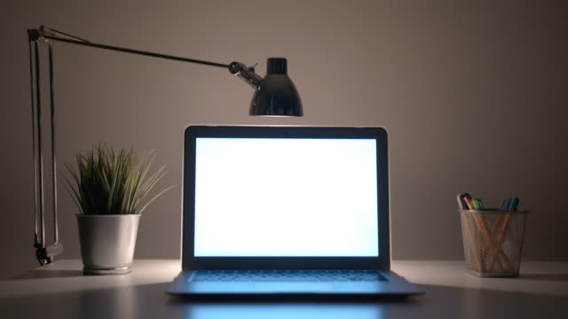 Laptop with a White Screen on the Table at Night