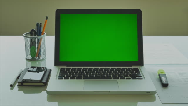 Laptop with green screen on modern glass table in the office 4K video