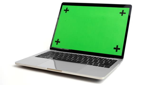 vidéos et rushes de ordinateur portable avec écran vert tournent sur fond blanc. - tourner
