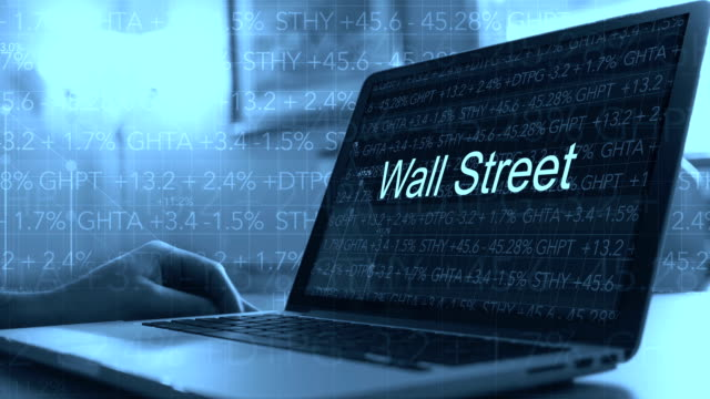 Laptop with stock market ticker scrolling in background with test on screen - Wall Street