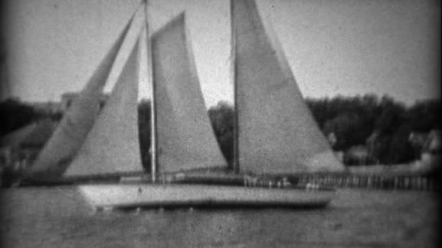 1934: Large 3 sailboat schooner across the pier event center and hillside mansions. video