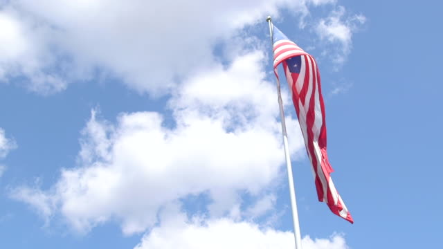 large american flag flying under bright blue cloudy sky - rispetto video stock e b–roll