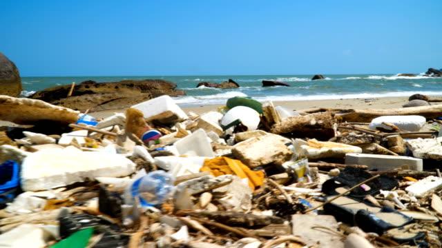 vídeos de stock e filmes b-roll de large amount of trash littering the ocean beach. plastic rubbish. - oceano pacífico