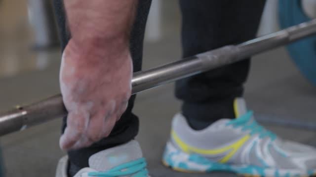 vídeos de stock, filmes e b-roll de um grande e poderoso halterofilista leva a campainha com a mão - braço humano