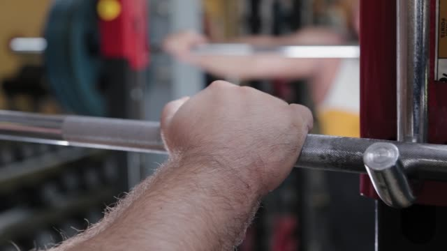 A large and powerful weightlifter takes the barbell with his hand