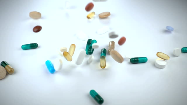 A large and varied assortment of pharmaceutical drugs or vitamin supplements fall in against a white background video