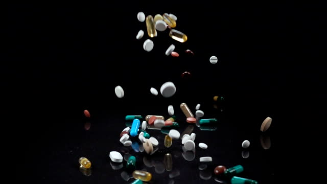 vídeos y material grabado en eventos de stock de caída de un grande y variado surtido de medicamentos o suplementos vitamínicos contra un fondo negro - píldoras