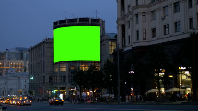 A large billboard, on an ancient building, on a busy street. Green screen. video