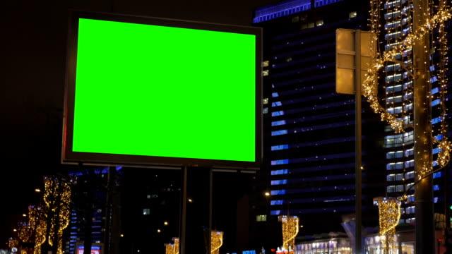 ein großes plakat auf der straße, umgeben von wunderschönen beleuchtung. - poster stock-videos und b-roll-filmmaterial