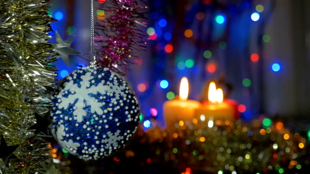 A large blue ball hangs on the Christmas tree. Blurred background video