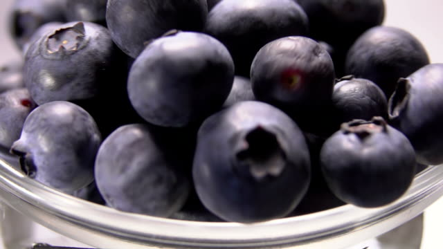 Large blueberries spilling out of a glass bowl video