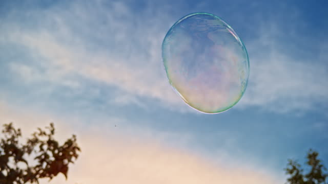 SLO MO Large bubble floating in the air outside with blue sky in the background Slow motion medium handheld shot of a large bubble floating in the air outside in the orchard with blue sky in the background. Shot in Slovenia. brightly lit stock videos & royalty-free footage
