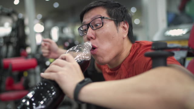 slo mo - large build man eating chip and drink soft drink while working out - obsoleto video stock e b–roll