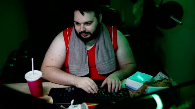 ビデオゲームをする大きなビルドマン - 不健康な食事点の映像素材/bロール