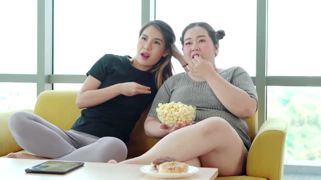 large build woman eating snack and watching television