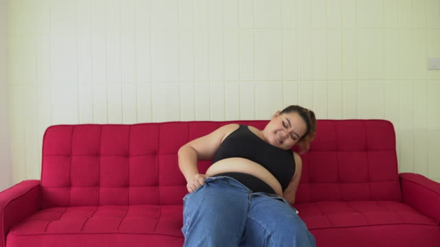 large build  woman trying to close the buttons of her jeans large build, Jeans, The Human Body, Large Build, Human Abdomen pinching stock videos & royalty-free footage