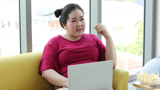 large build woman using notebook and tablet for working from home and asian girl enjoy eating food on sofa at home