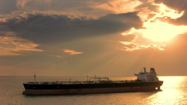 AERIAL Large cargo ship sailing the sea at sunset