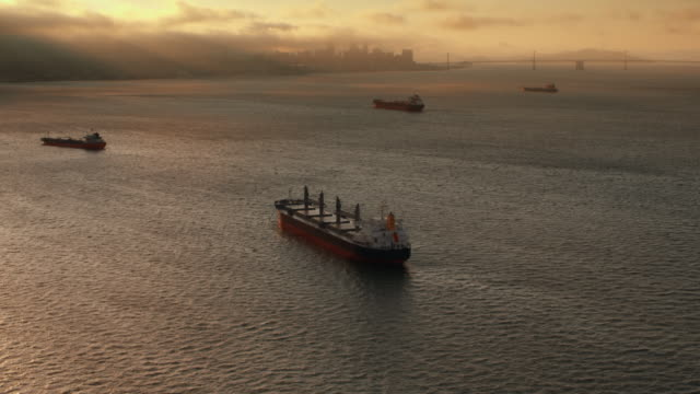 AERIAL Large cargo ships in the waters of San Francisco Bay at sunset
