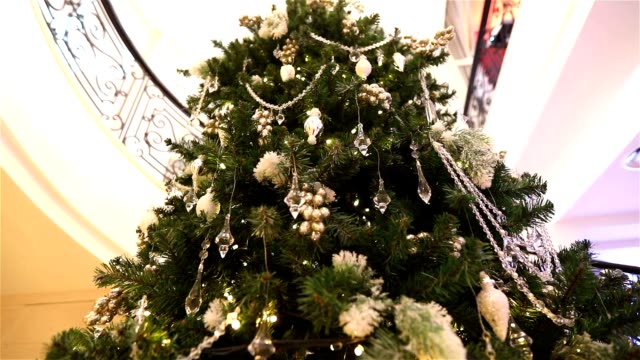 large Christmas tree in the lobby of the hotel, restaurant. Christmas tree in the hall on the background of the marble staircase with a handrail, bottom view video