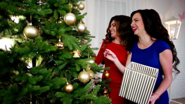 großer weihnachtsbaum mit goldenen kugeln und glitzernden girlanden, freundin in der nähe der weihnachtsbaum, vorbereitung für die silvester-party, mädchen in cocktailkleider, sagen sie, haben eine gute stimmung - kieferngewächse stock-videos und b-roll-filmmaterial
