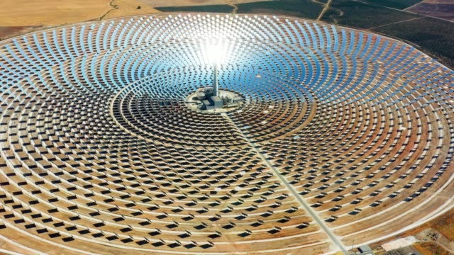 vídeos de stock e filmes b-roll de large circular power plant of solar panels in spain. there is the reflection of the sun in the the panels which produce renewable energy, solar energy - close-up view with a drone - environment concept - equipamento solar