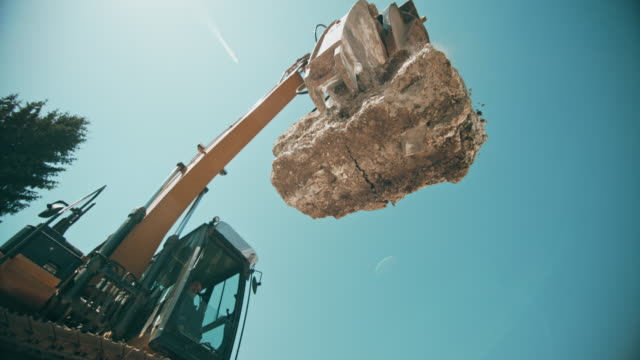 SLO MO Large concrete piece falling down and crushing as the excavator drops it