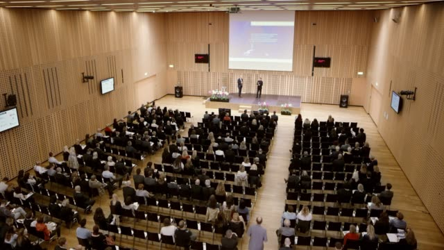 ld large conference hall with the seated seminar attendees and two speakers on the stage podium - struttura pubblica video stock e b–roll