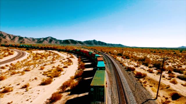 vídeos de stock, filmes e b-roll de um grande container locomotivo percorre uma ferrovia no deserto americano. - economy