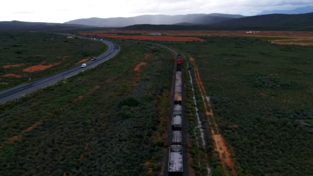 A large container locomotive travels down a railroad track