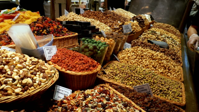 large counter of dried fruits and nuts at a farmers market in la boqueria. barcelona. spain - pinolo video stock e b–roll
