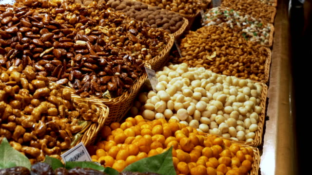 large counter of dried fruits, nuts and sweets at a market in la boqueria. barcelona. spain - pinolo video stock e b–roll