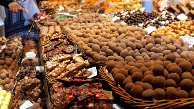 large counter of sweets with chocolate candy in la boqueria market in barcelona. spain - modella negozio video stock e b–roll