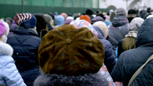 large crowd of people is walking along the city street. winter, snow is falling. - fuggitivo video stock e b–roll