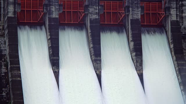 A large dam is discharged water from a pipeline, a source of hydroelectric power.
